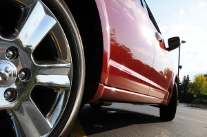 The passenger side and close-up of the rear wheel on a red Dodge Journey.